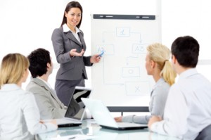 Successful business woman giving a presentation on flipchart.
